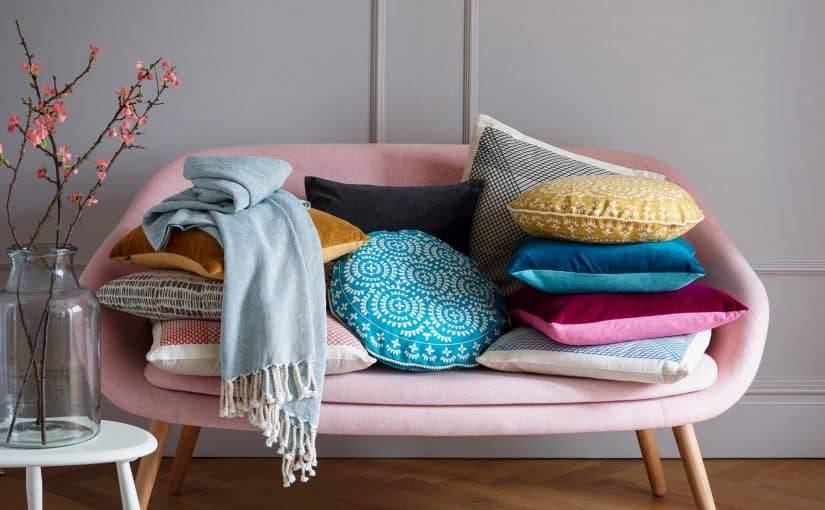 Ocado Pink Sofa with a decorative stack of cushion in differs colours, Yellow, pink, blue.