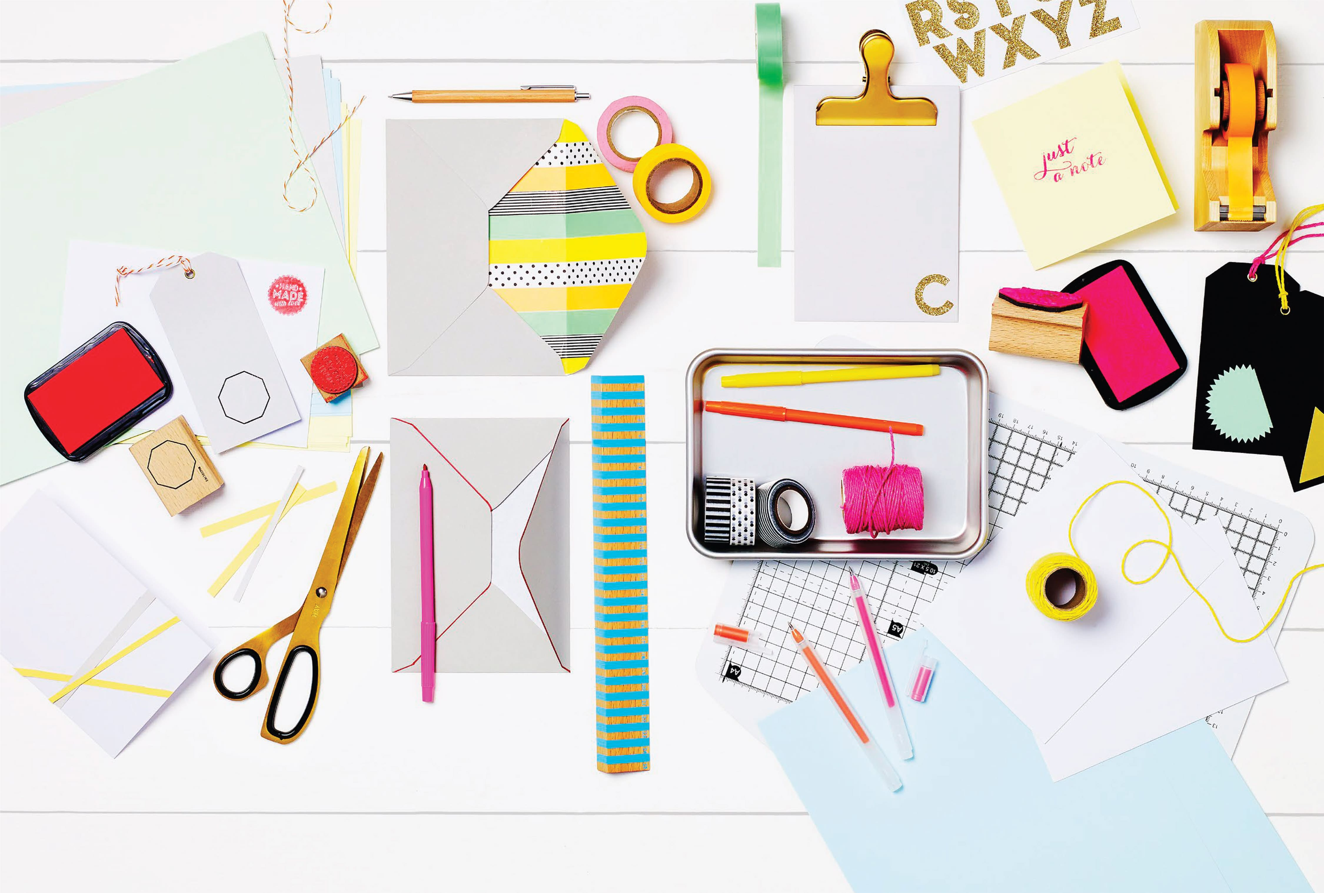 Overhead shot of colourful stationary with gold scissors and yellow washi tape