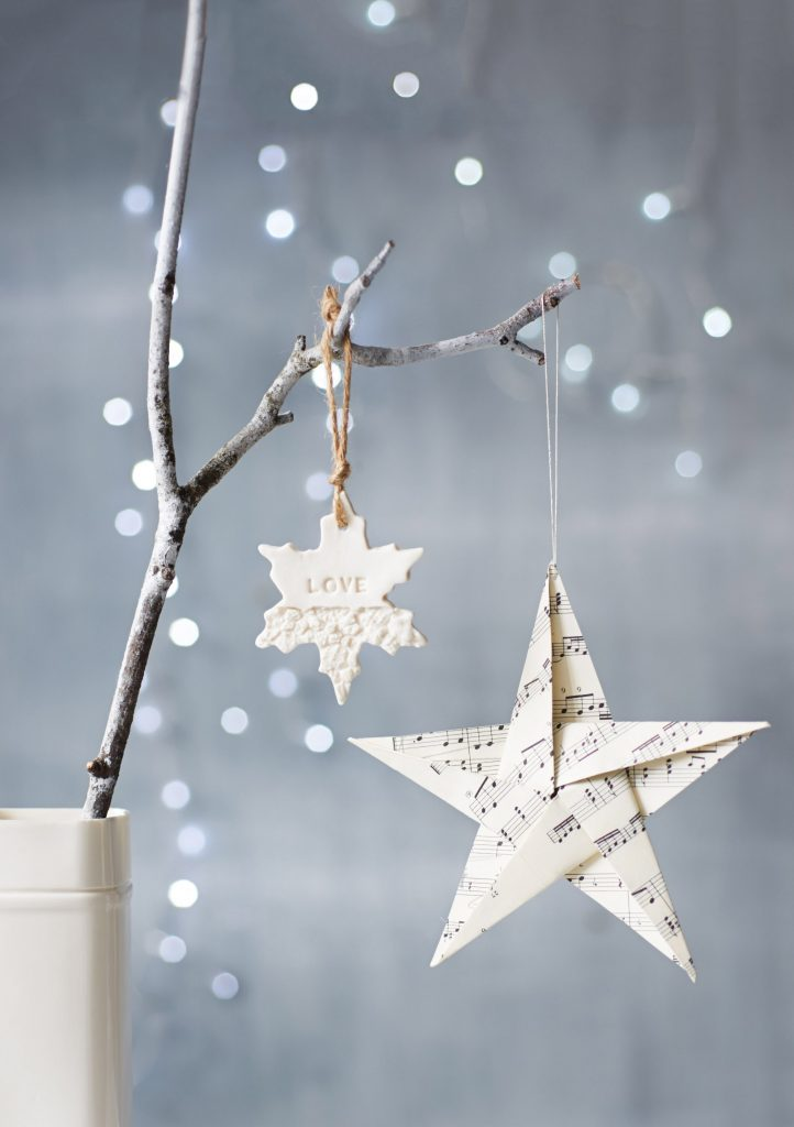 Christmas paper decorations hanging off a seasonal white branch, with fairy lights in the background