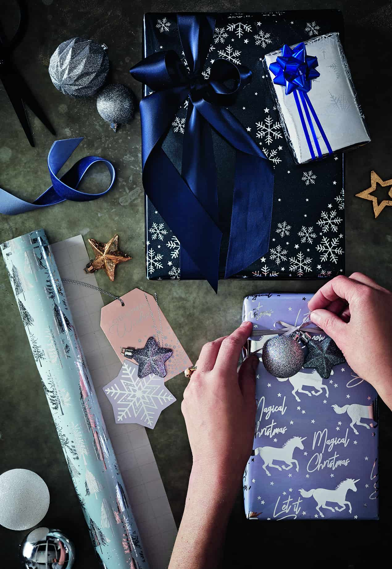 Adding the finishing touches to your Christmas presents with ribbon and baubles. finishing touches baubles tesco gift guide